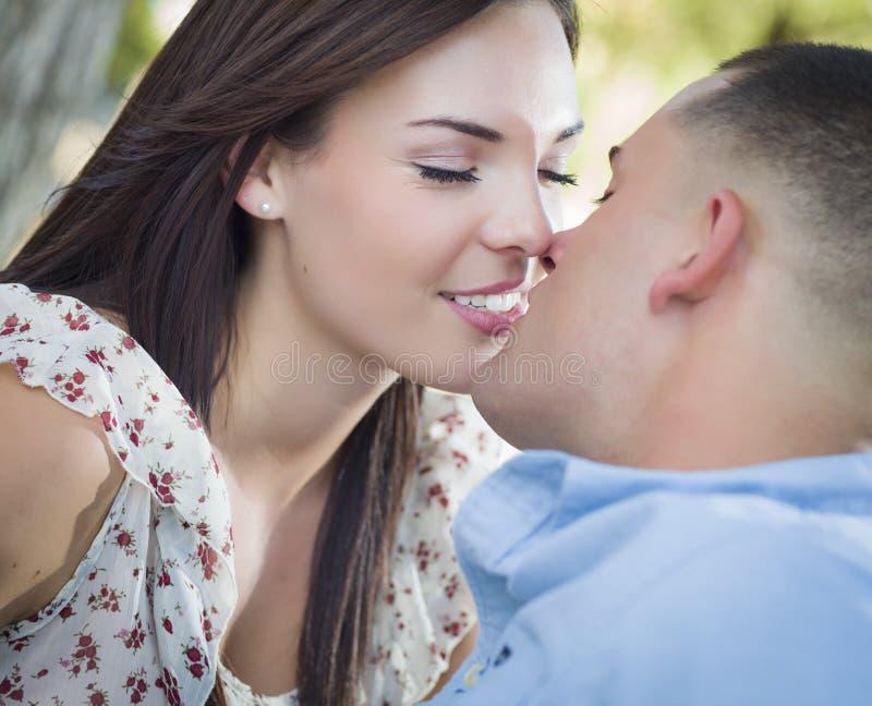 亲吻在公园的浪漫混合的族种夫妇 免版税库存照片