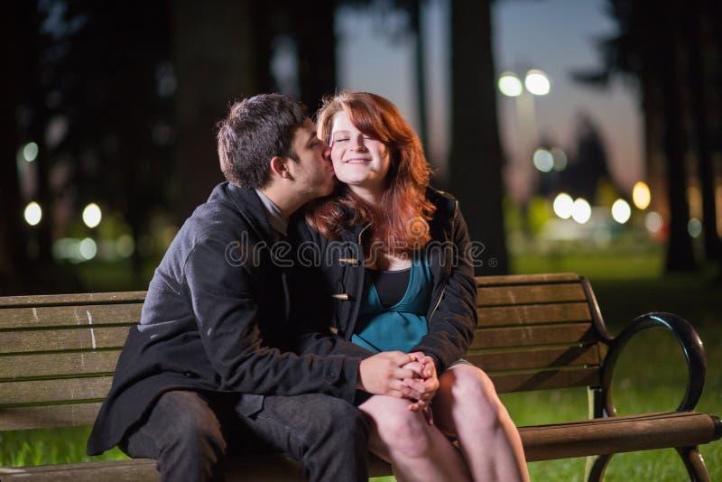亲吻在公园长椅的年轻夫妇在晚上 免版税库存照片