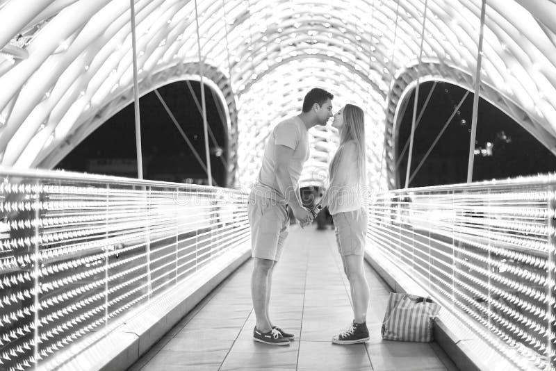 亲吻在和平桥梁的年轻爱恋的夫妇在第比利斯 免版税库存图片