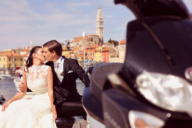 亲吻在城市的新娘和新郎在摩托车附近 免版税库存图片
