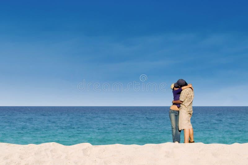 亲吻在天堂海滩的浪漫夫妇 免版税库存图片