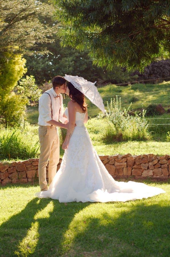 亲吻在庭院婚礼的新娘和新郎 免版税库存照片