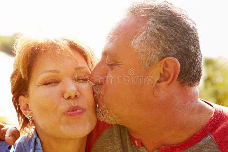 亲吻在庭院里的富感情的资深夫妇 库存照片
