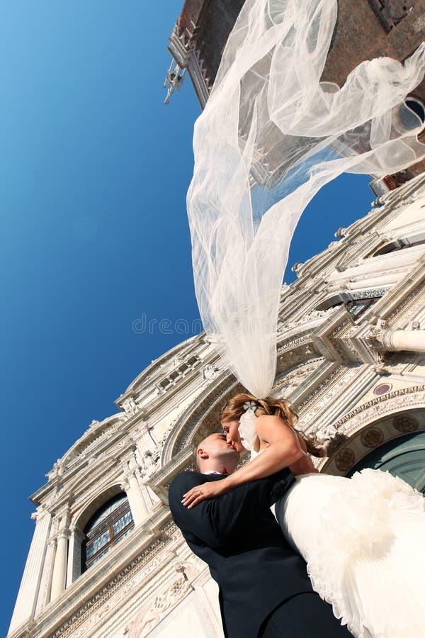 亲吻在教会前面的新娘和新郎 库存照片