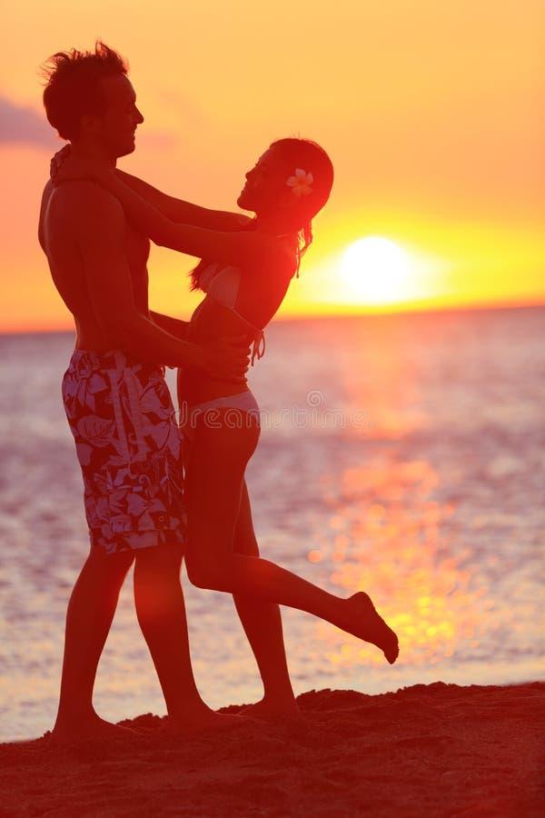 亲吻在旅行的海滩日落的浪漫夫妇 库存照片