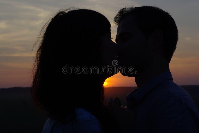 亲吻在日落的剪影夫妇 免版税库存照片