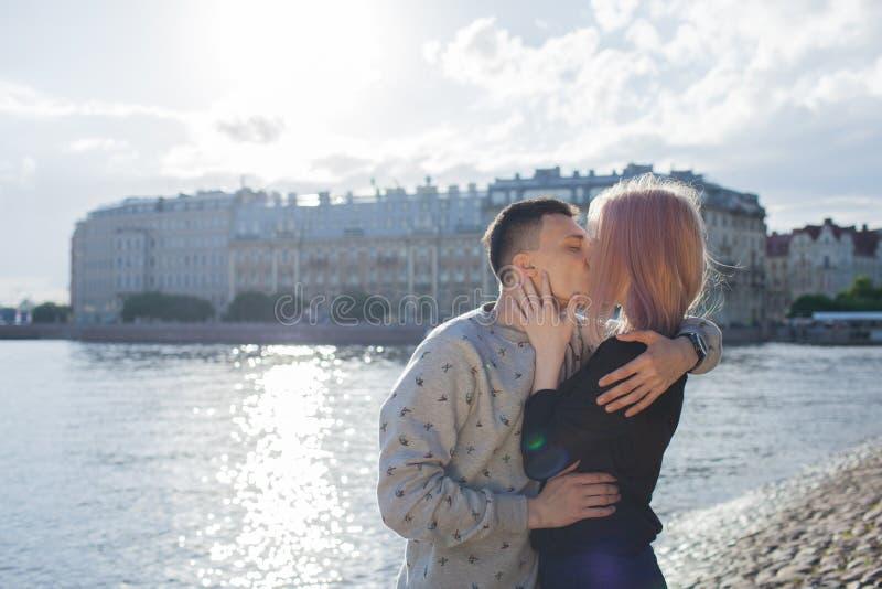 亲吻在江边的愉快的夫妇 免版税库存图片