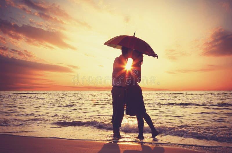 亲吻在海滩的夫妇 免版税库存图片