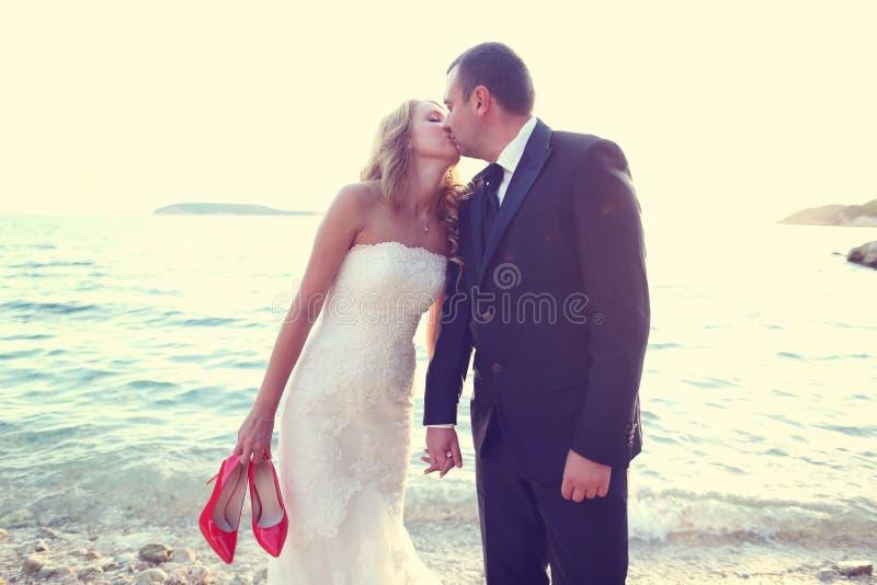 亲吻在海滩的新郎和新娘在一个晴天 免版税库存照片