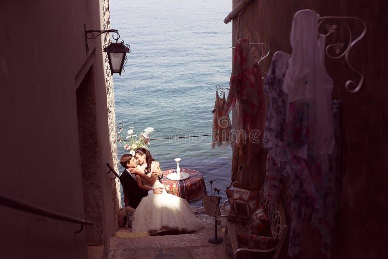 亲吻在海洋附近的新娘和新郎 免版税库存图片