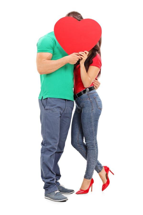 亲吻在红色心脏后的年轻夫妇 免版税库存图片