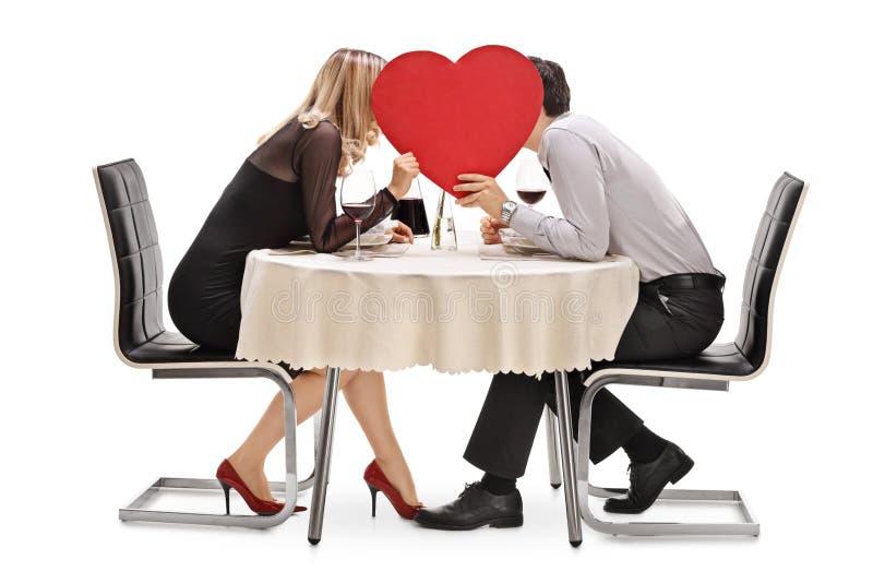 亲吻在红色心脏后的年轻夫妇 免版税库存照片