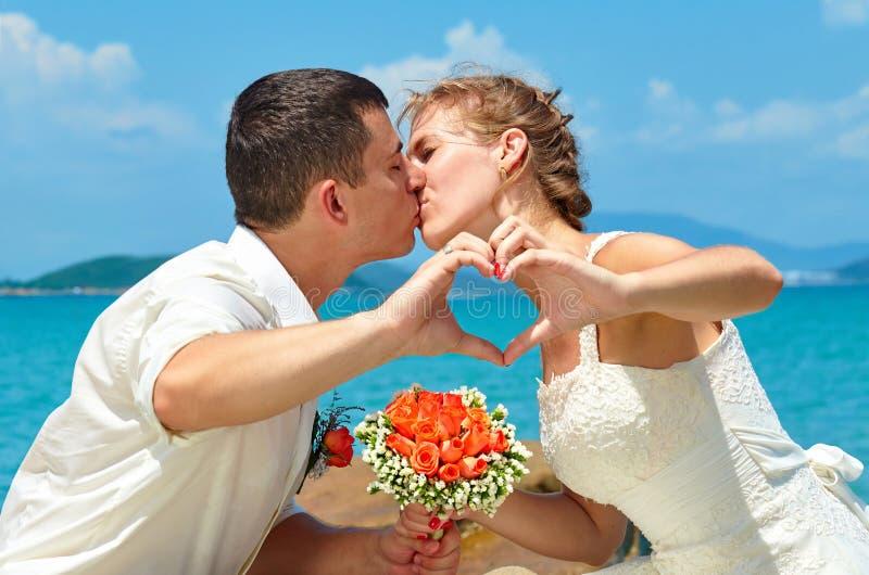 亲吻在美丽的热带海滩的新娘和新郎, romanti 免版税库存图片