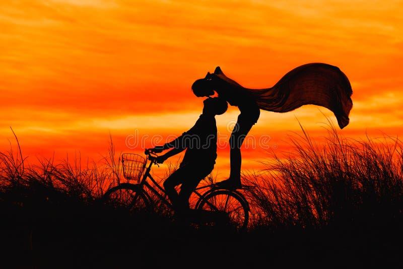 亲吻在自行车的剪影夫妇 免版税库存图片