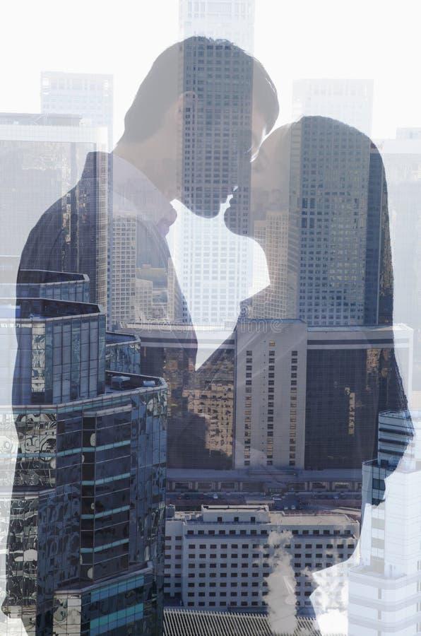 亲吻在都市风景,侧视图,剪影的夫妇两次曝光  库存照片