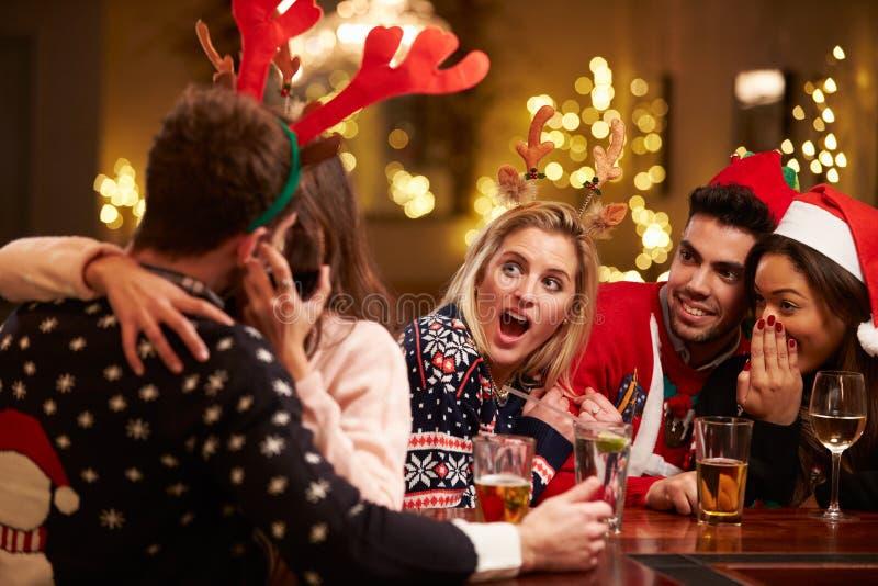 亲吻在酒吧的夫妇作为朋友享受圣诞节饮料 免版税图库摄影