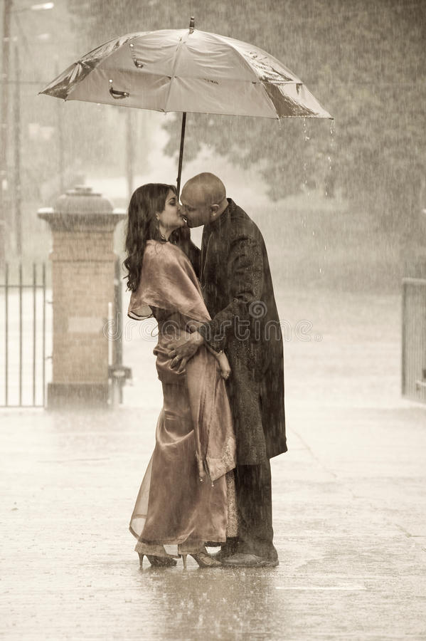 亲吻在雨ki的一把伞下的印地安夫妇 免版税库存照片