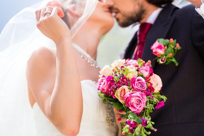 亲吻在面纱下的新娘对在婚礼 免版税库存照片