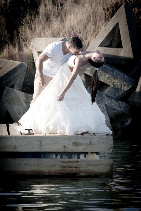 亲吻在水的边缘的年轻美好的新娘夫妇 库存照片