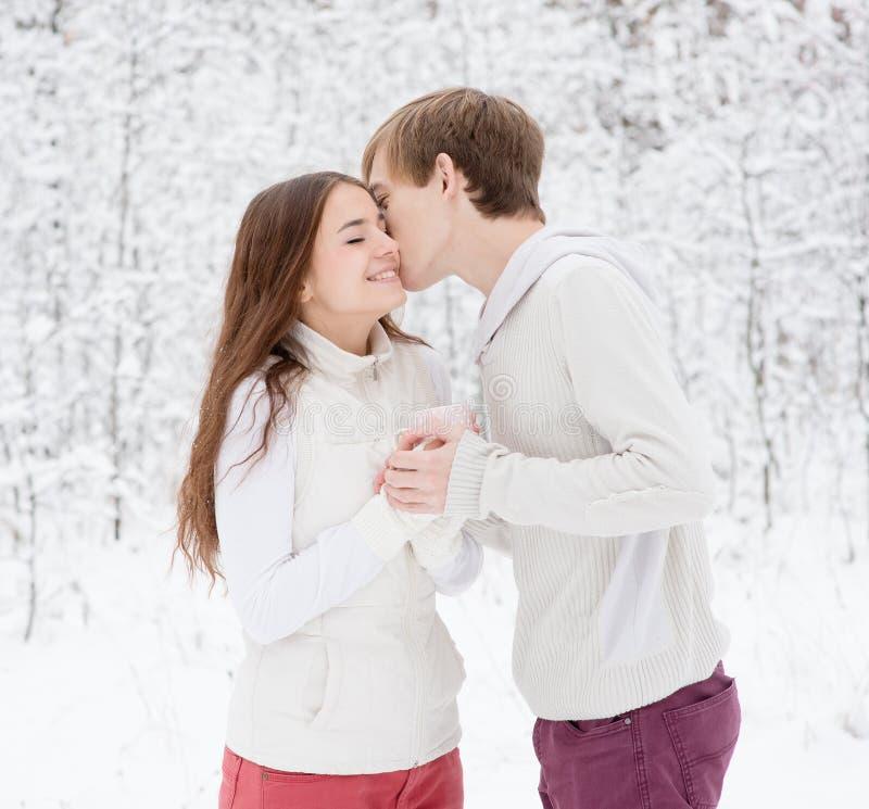 亲吻女孩的男孩在冬天森林里 免版税库存照片