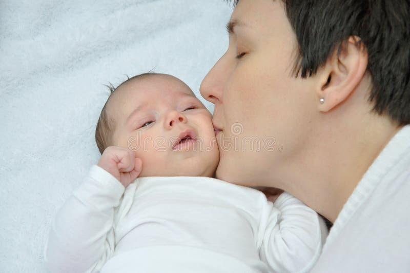 亲吻她新出生的女婴的母亲 免版税库存照片