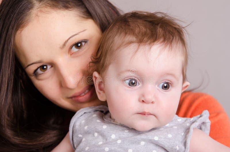 亲吻她的女儿的年轻愉快的母亲 库存照片