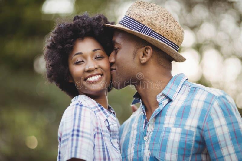 亲吻她的女朋友面颊的微笑的人 库存照片