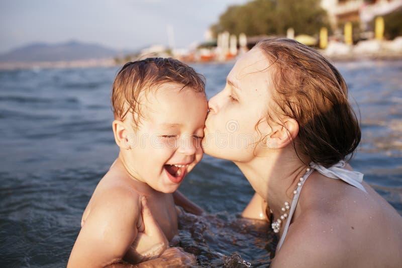 亲吻她的幼儿的母亲 免版税图库摄影