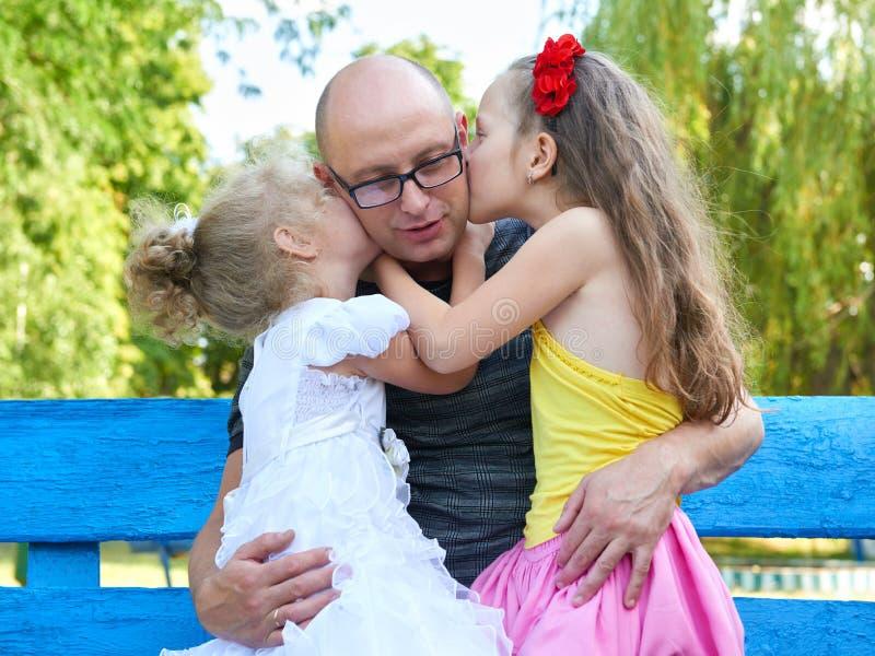 亲吻她的父亲,愉快的家庭画象,小组的儿童女孩三人坐长凳,育儿概念 图库摄影