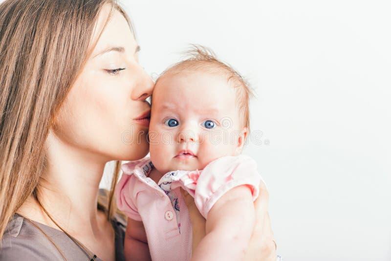 亲吻她的婴孩的愉快的母亲在白色背景 免版税库存照片