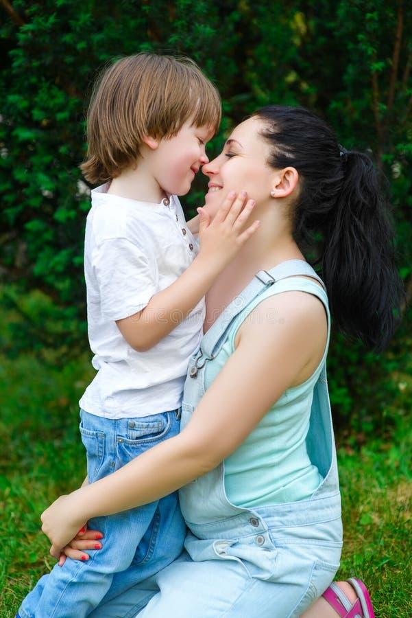 亲吻他鼻子的爱恋的儿子愉快的母亲 免版税库存图片