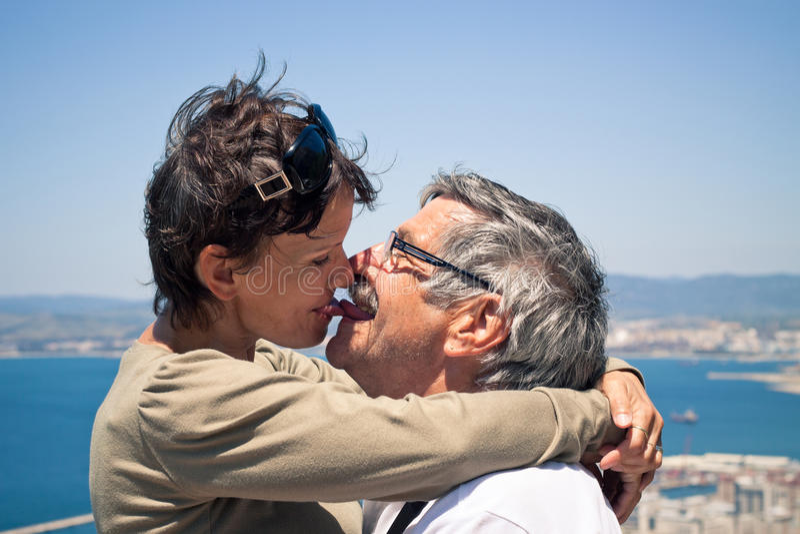 亲吻愉快的夫妇户外 免版税库存图片