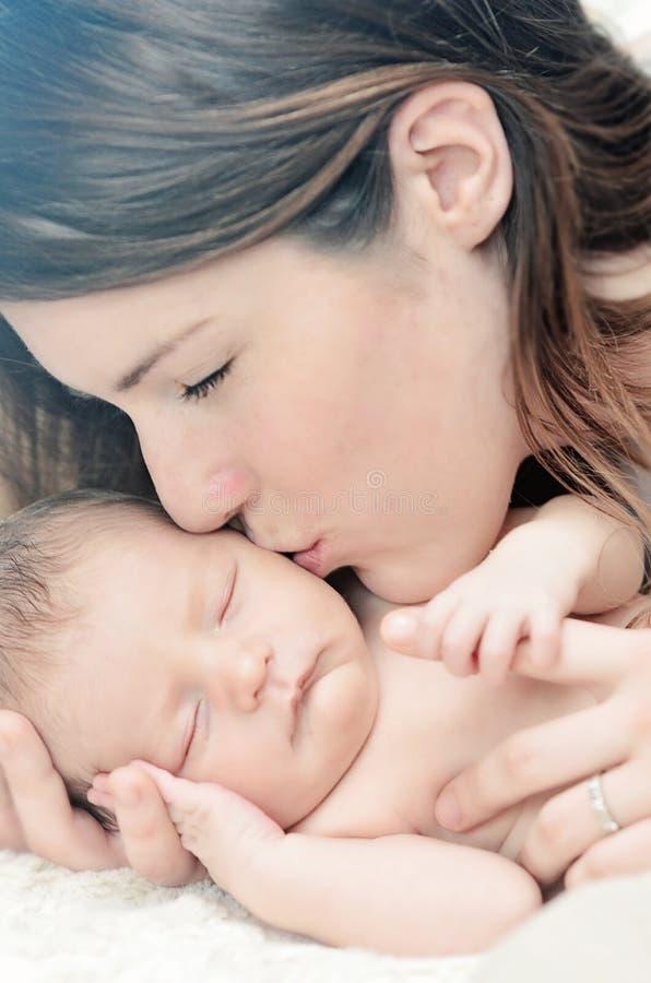 亲吻新出生的婴孩的母亲