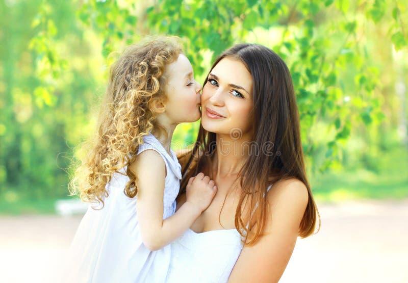 亲吻母亲、愉快的年轻妈妈和孩子的爱恋的女儿在温暖的晴朗的夏日在自然 免版税库存照片