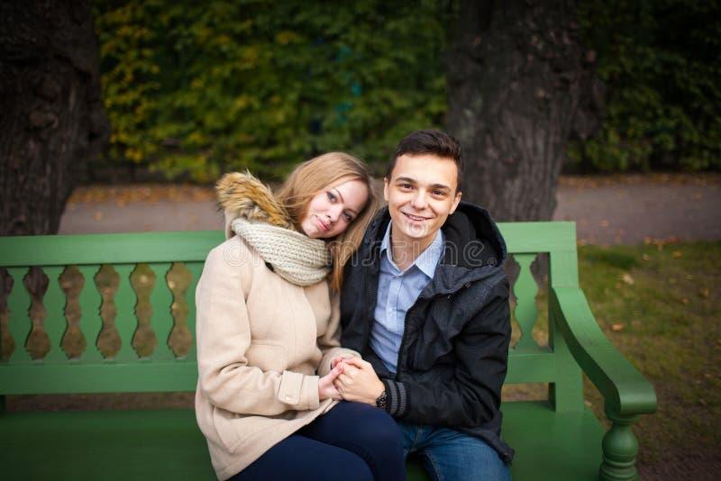年轻亲吻男孩和的女孩拥抱和,坐长凳 库存照片