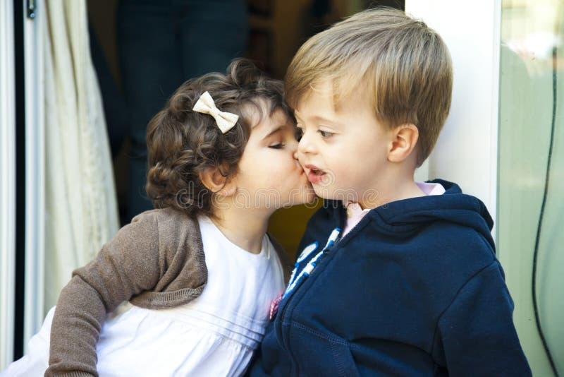 亲吻男孩的中景女孩 免版税库存图片