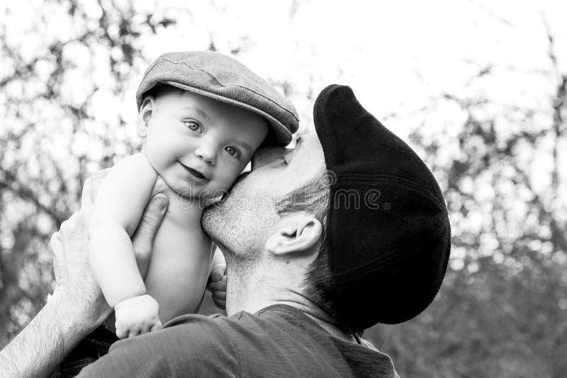 亲吻他的儿子黑白照片的父亲 免版税库存照片
