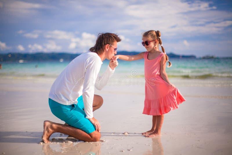 亲吻他的小女儿的手的爸爸  免版税库存图片