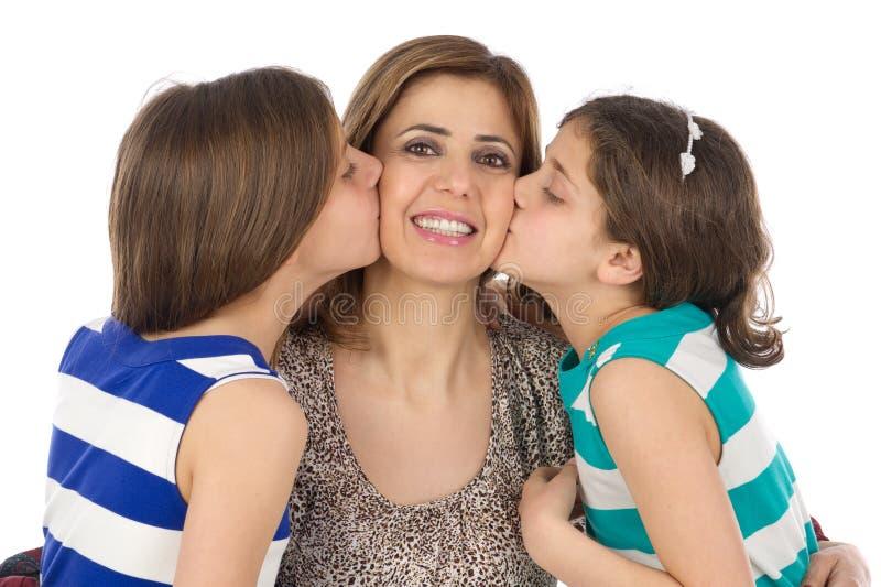 亲吻他们的母亲的两个女儿 库存图片