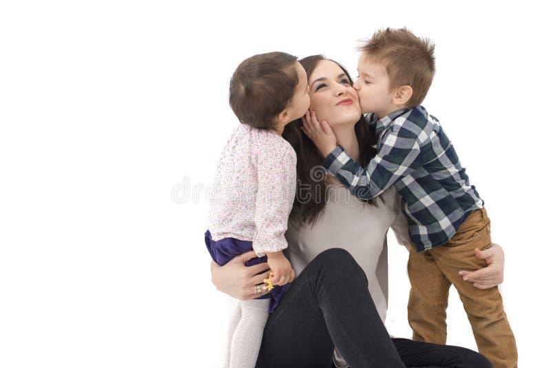 亲吻他们的母亲的小女孩和男孩被隔绝 库存照片