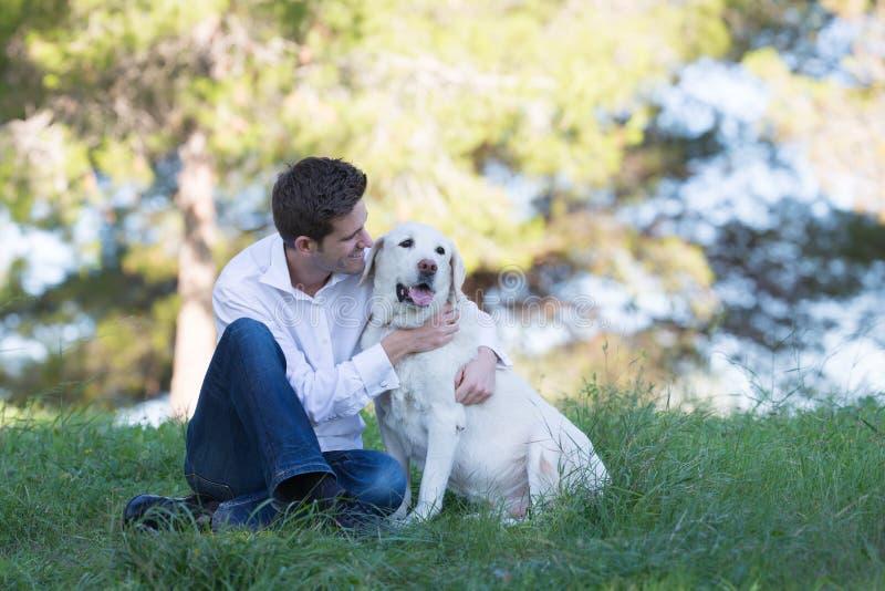 亲吻他的资深拉布拉多狗的年轻人 库存照片