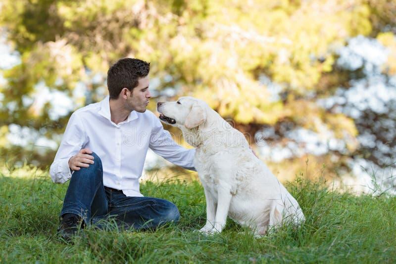亲吻他的非常老狗的年轻人在公园 免版税库存照片
