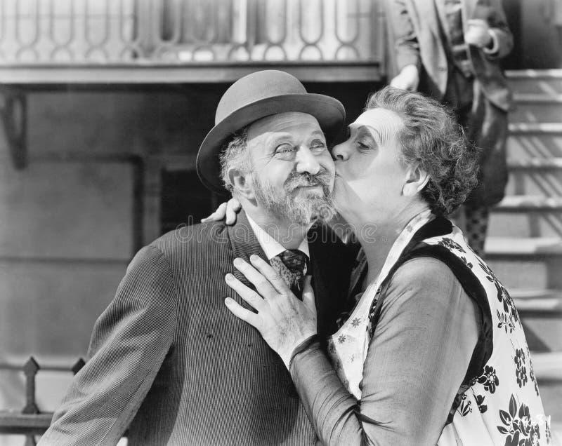 亲吻他的面颊的妇女一个人(所有人被描述不更长生存,并且庄园不存在 供应商保单那里 图库摄影
