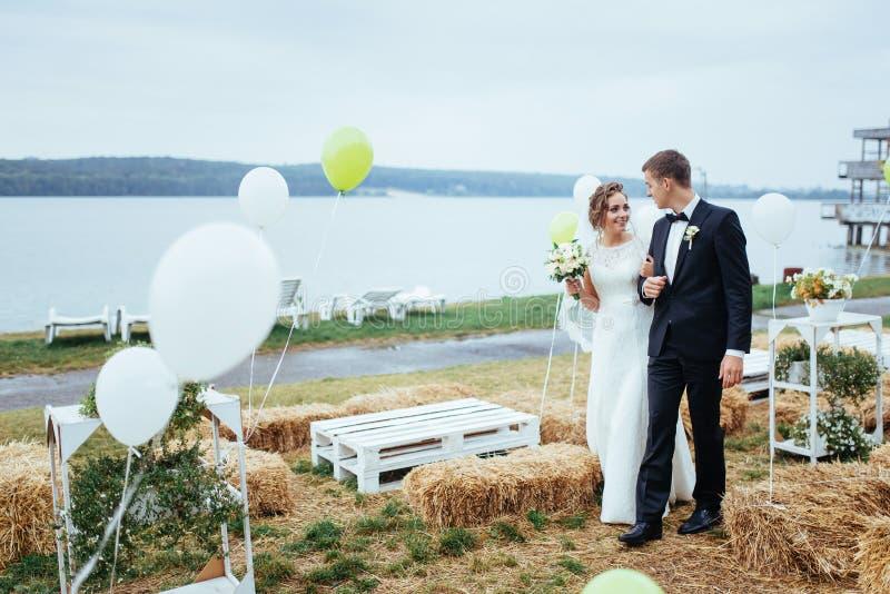 亲吻美好的年轻婚礼的夫妇,有flowe的白肤金发的新娘 免版税库存图片