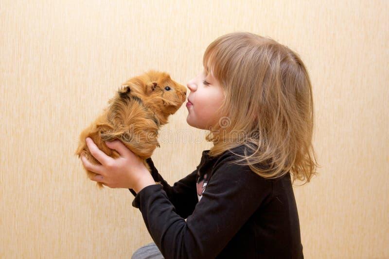 亲吻试验品的孩子。对动物的爱 图库摄影