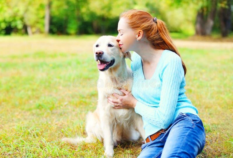 亲吻金毛猎犬狗的愉快的所有者妇女 免版税库存照片