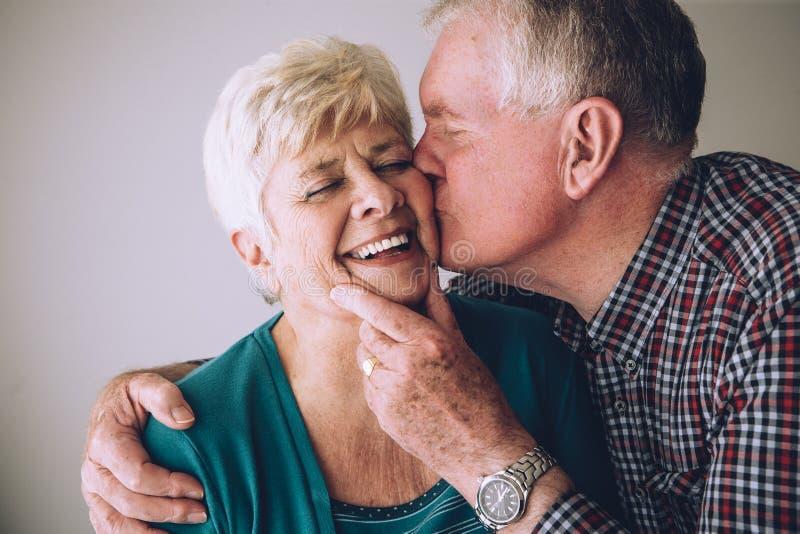 亲吻面颊的老人妻子 免版税图库摄影