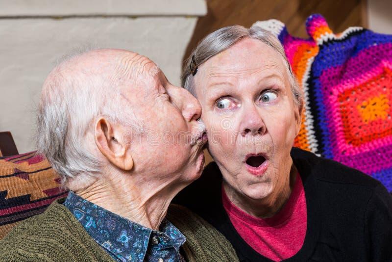 亲吻面颊的年长绅士年长妇女 免版税库存图片