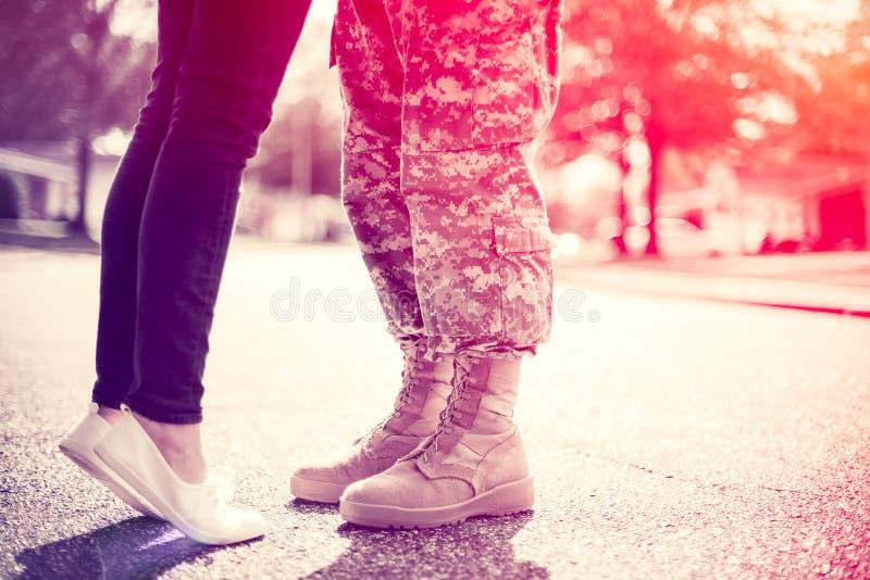 亲吻,归乡概念的年轻军事夫妇 免版税库存图片