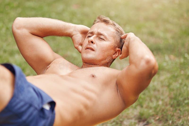 人、体育、生活方式和耐力概念 有stong身体的运动的年轻男性爱好健美者,做咬嚼,有室外训练 库存图片